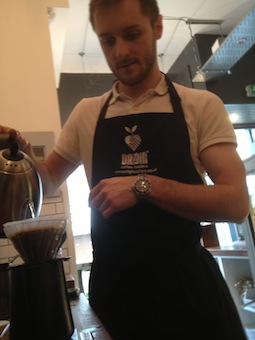 A barista brewing coffee in a hario V60