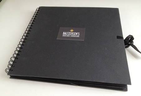 A black book with a Baltzersen's business card ont he front ready for storytelling