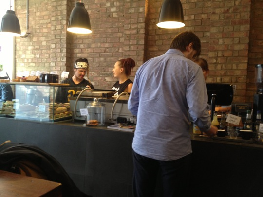 Counter with two baristas working at Kaffeine in Great Titchfield St, London.