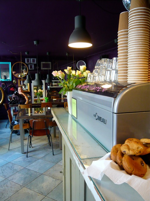 Cimbali coffee machine on counter, mirrors mounted on purple back wall