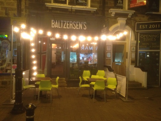 Baltzersen's shop front with a string of festoon lights - bulbs on a string.