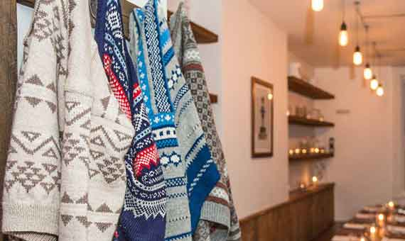 Photo of jumpers hung up and candles lit in Baltzersen's Scandinavian cafe in Harrogate, trying to show an example of hygge