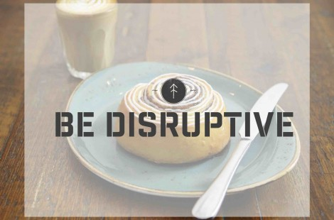 A photo of a Baltzersen's cinnamon bun with the word 'Be Disruptive' written across.
