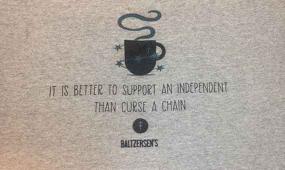 Photo of Baltzersen's t-shirt with caption 'it's better to support an independent than curse a chain'