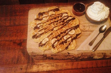 Photo of waffles with chocolate sauce and banana on them for International Waffles Day in Scandinavian cafe Baltzersen's in Harrogate